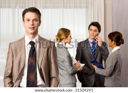 Portrait of handsome employer smiling at camera with consulting staff on background