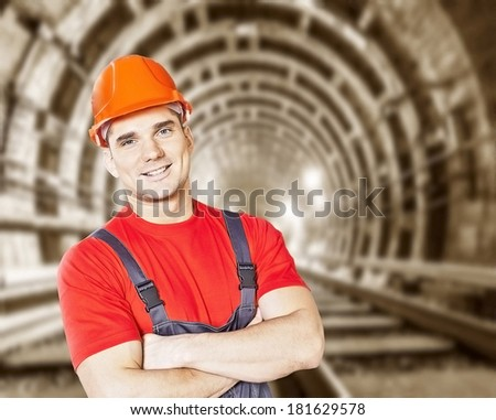 Portrait of handsome engineer  with orange helmet for workers security against the background of an underground mine with arc legs and rails for trolleys with coal in perspective - stock photo