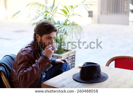 Portrait of handsome fashionable hipster man holding cup of tea or coffee next to his mouth while sitting on the terrace of beautiful coffee shop - stock photo