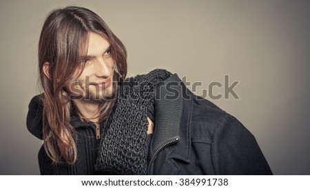 Portrait of handsome fashionable man wearing black sweater and scarf holding coat. Young guy posing in studio. Winter or autumn fashion. Instagram filter. - stock photo