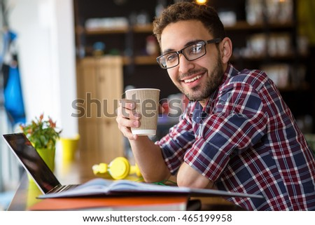 Portrait of handsome freelance man in glasses sitting with cup of coffee. Cheerful attractive man working on laptop computer.
