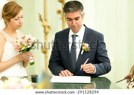 Portrait of handsome groom signing contract at wedding ceremony