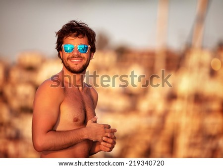 Portrait of handsome guy on the beach in mild yellow sunset light, perfect athletic body, summer vacation on luxury sailboat  - stock photo