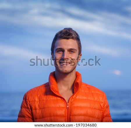 Portrait of handsome happy active young adult man in orange jacket outdoors. - stock photo