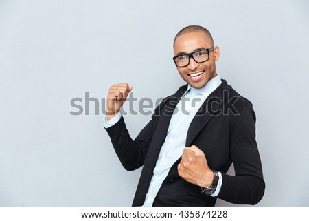 Portrait of handsome happy african american young man celebrating success - stock photo