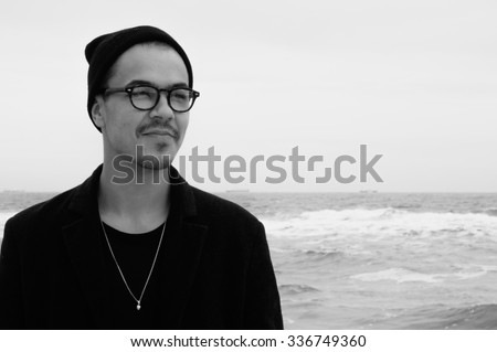 portrait of handsome hipster guy in glasses and hat on hazy cold sea background black and white - stock photo