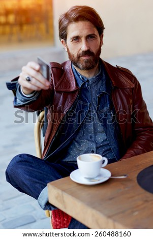 Portrait of handsome hipster man paying for his coffee with a credit card at the cafe, customer paying at a coffee shop with a credit card, flare sun light - stock photo