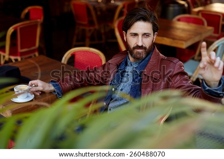 Portrait of handsome hipster man with beard man asking for a bill while sitting in a restaurant terrace - stock photo