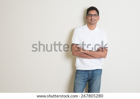 Portrait of handsome Indian guy standing on plain background with shadow and copy space. - stock photo