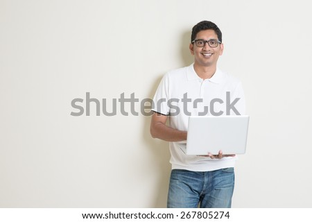 Portrait of handsome Indian guy using laptop computer, standing on plain background with shadow, copy space at side. - stock photo