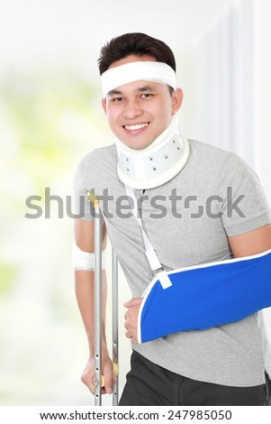 portrait of handsome injured young man but still feel happy - stock photo