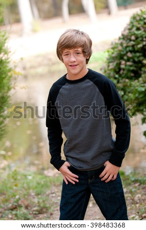 Portrait of handsome kid standing at a park wearing jeans and long sleeve black and grey shirt.