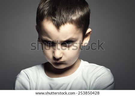 Portrait of handsome kid with angry face against grey background. - stock photo