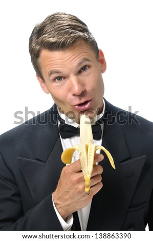 Portrait of handsome male Caucasian host in black tuxedo singing into a banana microphone with white background