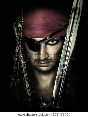 Portrait of handsome male pirate holding sword on black background - stock photo
