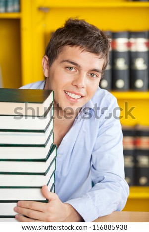 Portrait of handsome male student with stacked books smiling at table in university library