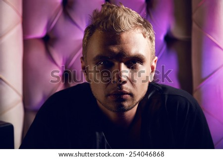 Portrait of handsome man blonde hair sitting on the chair in the shadow