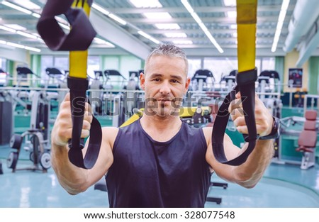 Portrait of handsome man doing hard suspension training with fitness straps in a fitness center. Healthy and sporty lifestyle concept. - stock photo