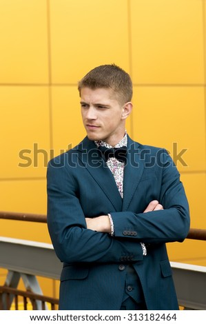 Portrait of handsome man in blue suit over yellow background.  - stock photo