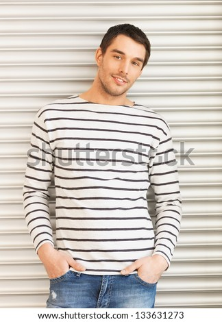 portrait of handsome man in casual clothes leaning to wall