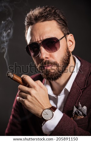 Portrait of handsome man in casual dress smoking a cigar. - stock photo