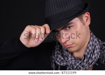 Portrait of handsome man in classic hat over black background