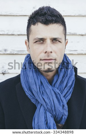 Portrait of handsome man in coat on white wooden background,selective focus - stock photo