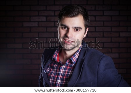 portrait of handsome man in jacket and plaid shirt - stock photo
