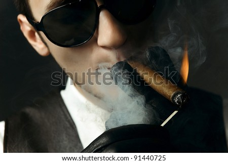 portrait of handsome man in shirt and vest over dark background smoking a cigar - stock photo