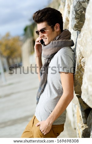 Portrait of handsome man in urban background talking on phone - stock photo
