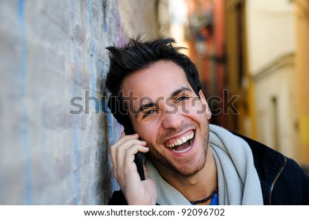 Portrait of handsome man in urban background talking on phone and laughing - stock photo