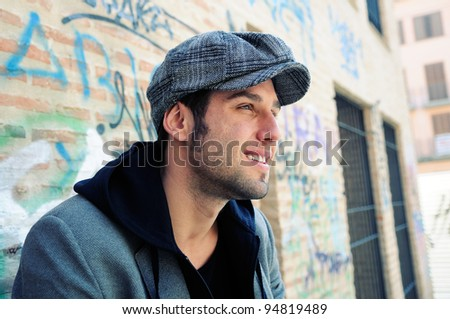 Portrait of handsome man in urban background wearing a retro cap - stock photo