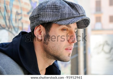 Portrait of handsome man in urban background wearing a retro cap