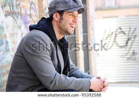 Portrait of handsome man in urban background wearing a retro cap and smiling - stock photo
