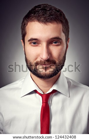 portrait of handsome man in white shirt and red necktie over grey background - stock photo