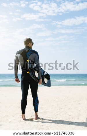 Portrait of handsome man kitesurfer in the beach.