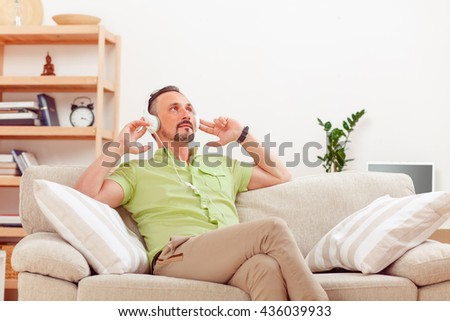 Portrait of handsome man listening to music at home while sitting on sofa or couch. Happy man relaxing and resting.