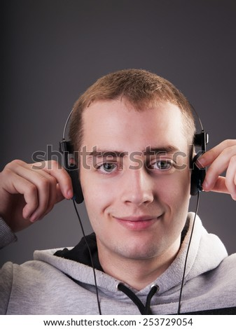Portrait of handsome man listening to music in headphones on gray background - stock photo