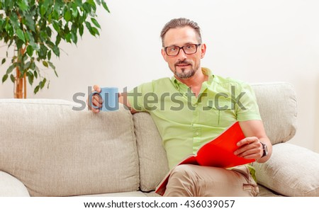 Portrait of handsome man looking at documents and drinking delicious cup of coffee or tea. Man in glasses working from home.