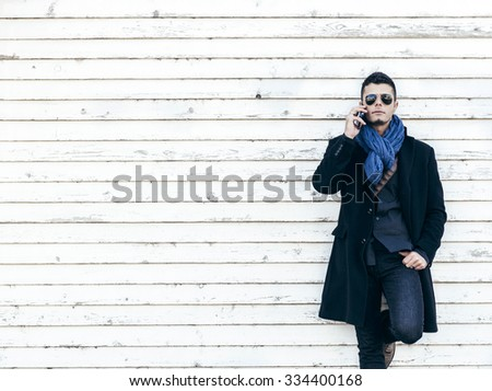 Portrait of handsome man on the phone on white wooden background with blank space,selective focus - stock photo