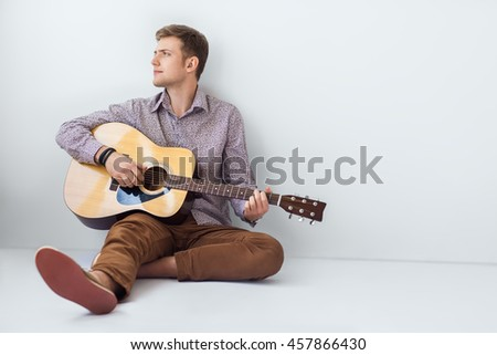 Portrait of handsome man playing guitar siting on floor with copy space