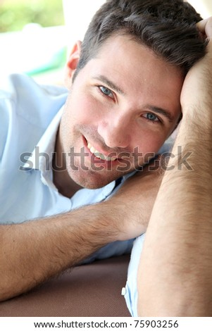 Portrait of handsome man sitting in sofa - stock photo
