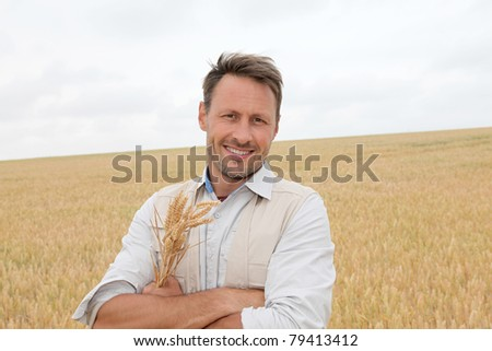 Portrait of handsome man standing in wheat field