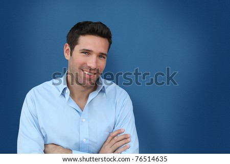 Portrait of handsome man standing on blue background - stock photo