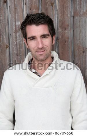 Portrait of handsome man standing on wooden door - stock photo