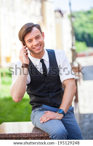 Portrait of handsome man talking on the cell phone with smile, urban background - stock photo