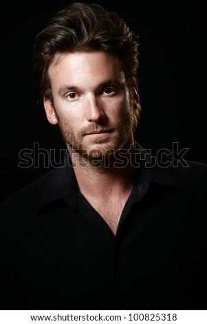 Portrait of handsome man wearing black shirt, black background, looking at camera. - stock photo