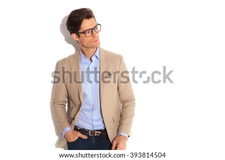 portrait of handsome man wearing glasses while posing with hand in pocket, looking away from the camera in isolated studio background - stock photo