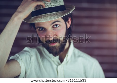 Portrait of handsome man wearing hat against wall