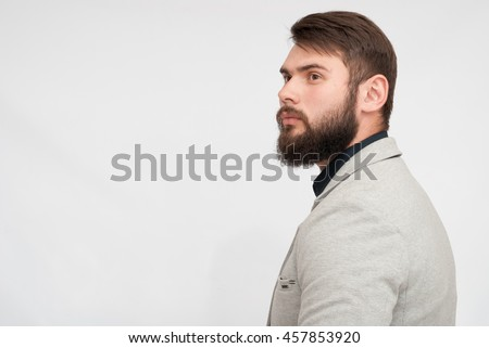 Portrait of handsome man with beard. man in jacket looking from behind